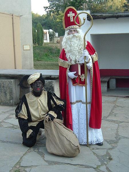 Sinterklaas w stroju biskupa i jego ciemnoskóry pomocnik. Zdjęcie na licencji Creative Commons. Autor: Looi