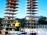 Badanie dwóch konstrukcji na stole wibracyjnym. Model konstrukcji z prawej jest wyposażony w system izolowania podstawy, a z lewej to konstrukcja klasyczna pozbawiona zabezpieczeń.